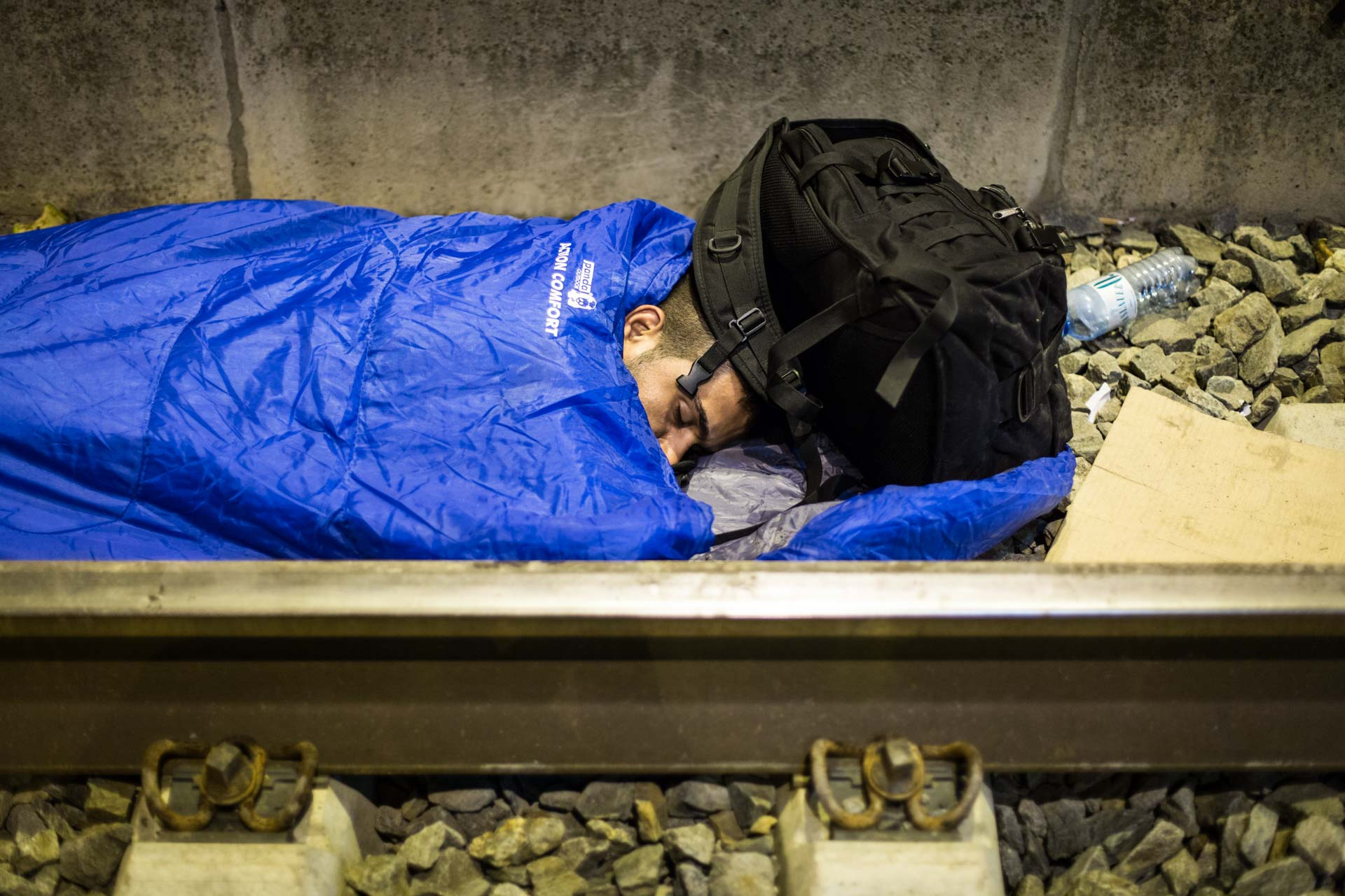 A man is spending the night next to a rail in front of the train station in Tovarnik, Croatia, waiting for a train to Slovenia.