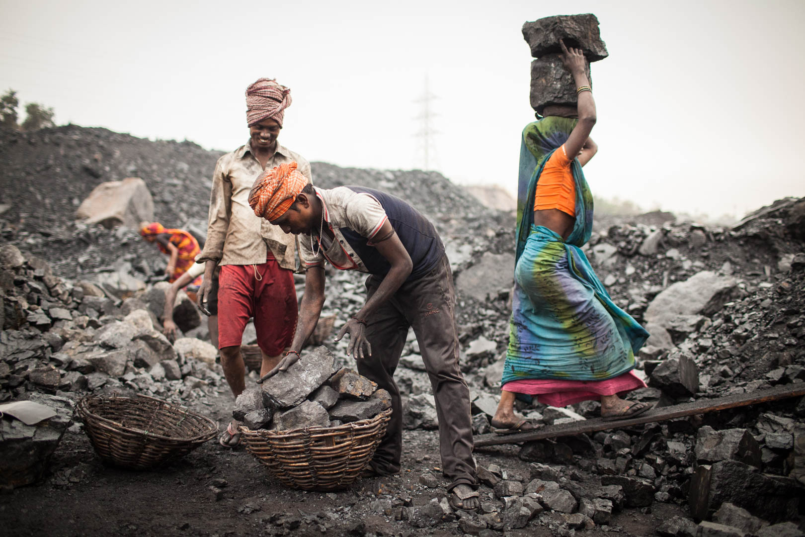 A group of workers are transporting the  coal that they have collected in the morning to a nearby truck.