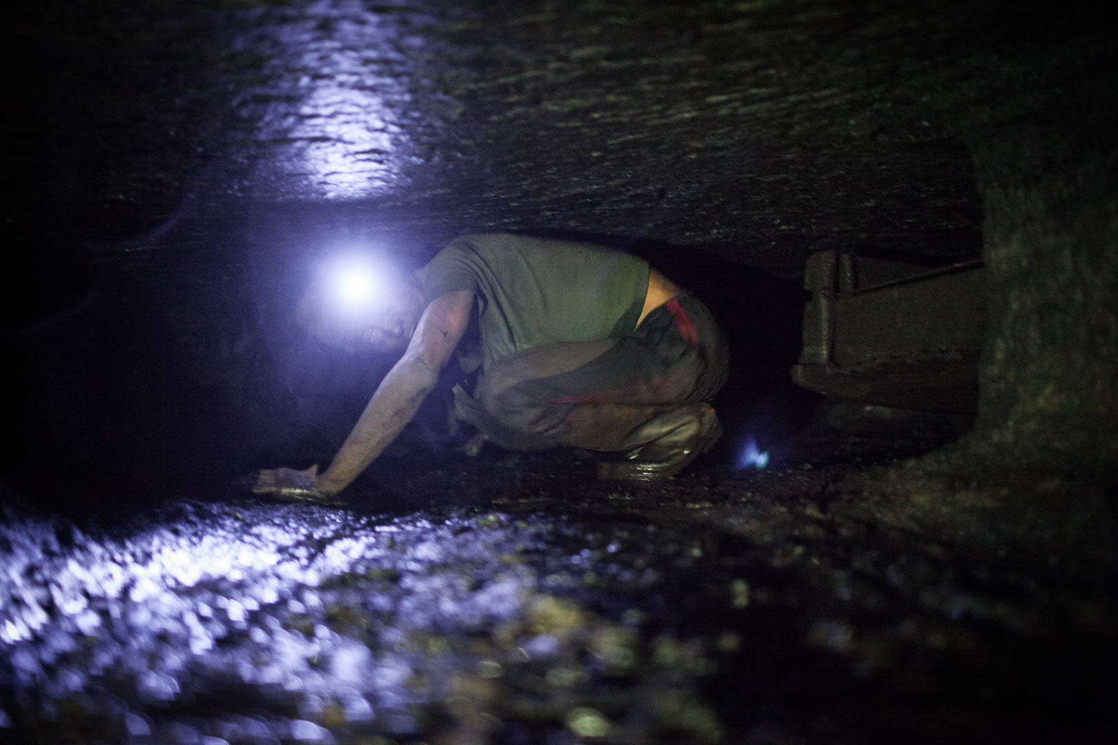 An Indian worker robs through a tunnel in one of the underground mines. Due to the illegal nature of the tunnels, the absence of government, and the greed of the mine owners, they lack any ventilation, stabilization or illumination.