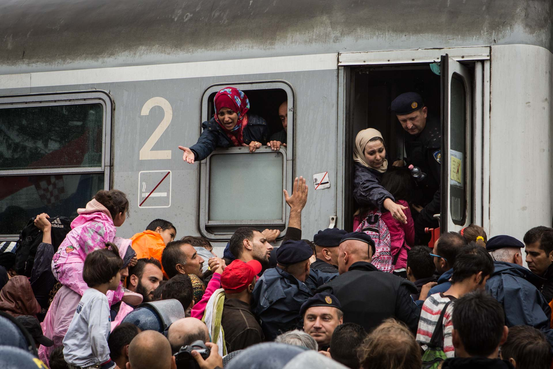 A mother on a train to Slovenia is screaming at the top of her lungs to get her child trapped in a crows of people.