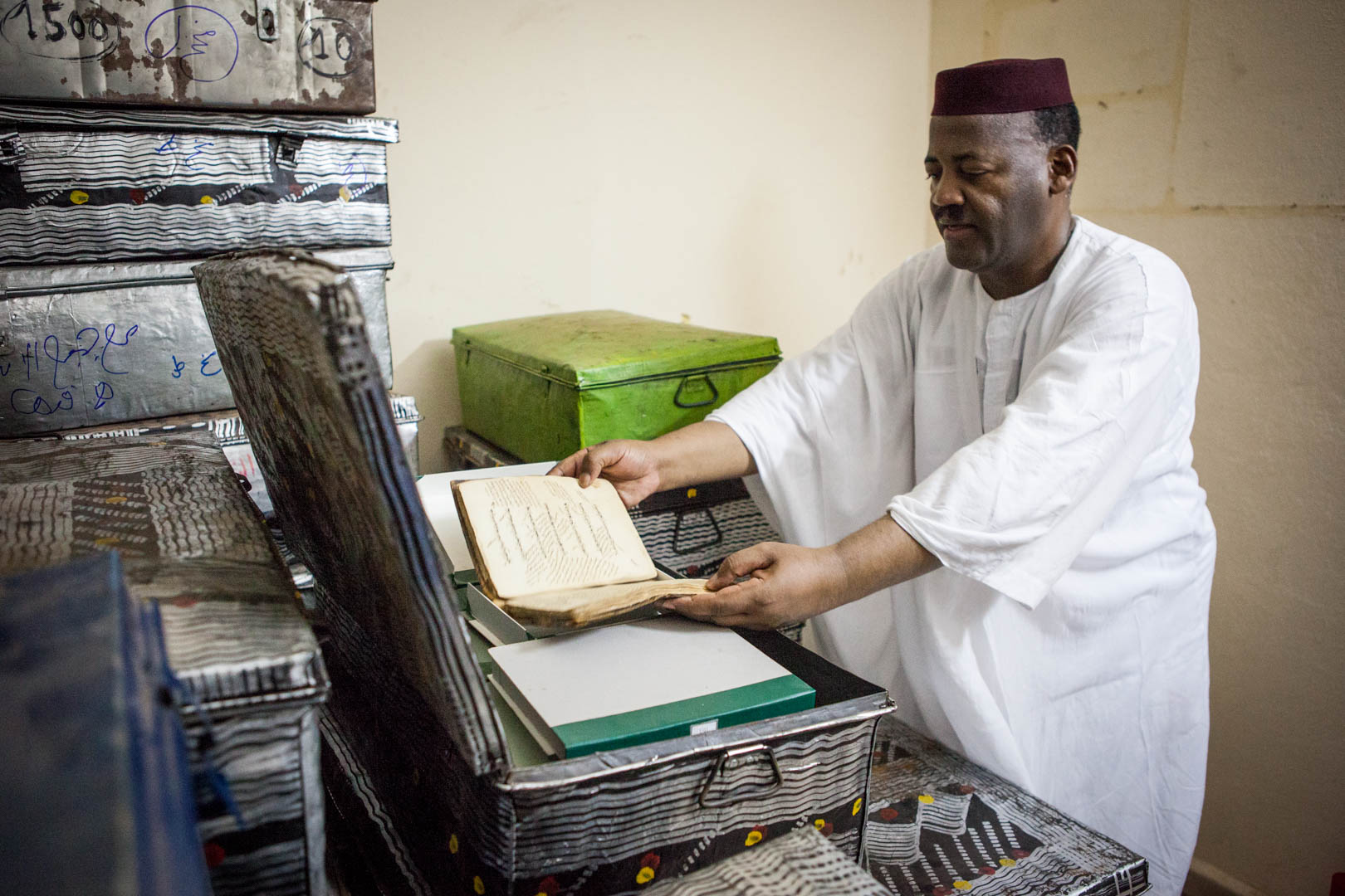 Abdel Kader Haidara, the head of the Haidara private Library in Timbuktu, checks the condition of a manuscript in their storage room in Bamako. He was a major figure behind the exodus that the manuscripts from Timbuktu went through.