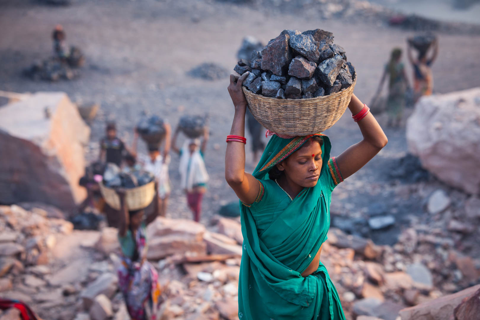 A young woman is carrying coal in a basket to a collecting spot. Men and woman alike miss school and other educational opportunities for their work in the mines.