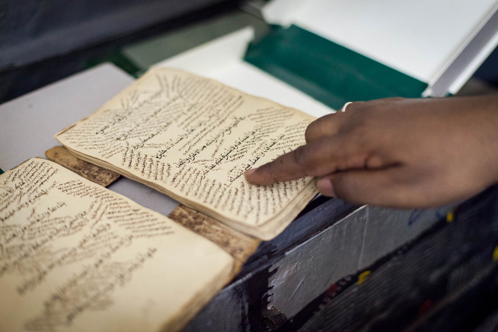 Abdel Kader Haidara points his finger on a document that used to be stored in his library in Timbuktu.