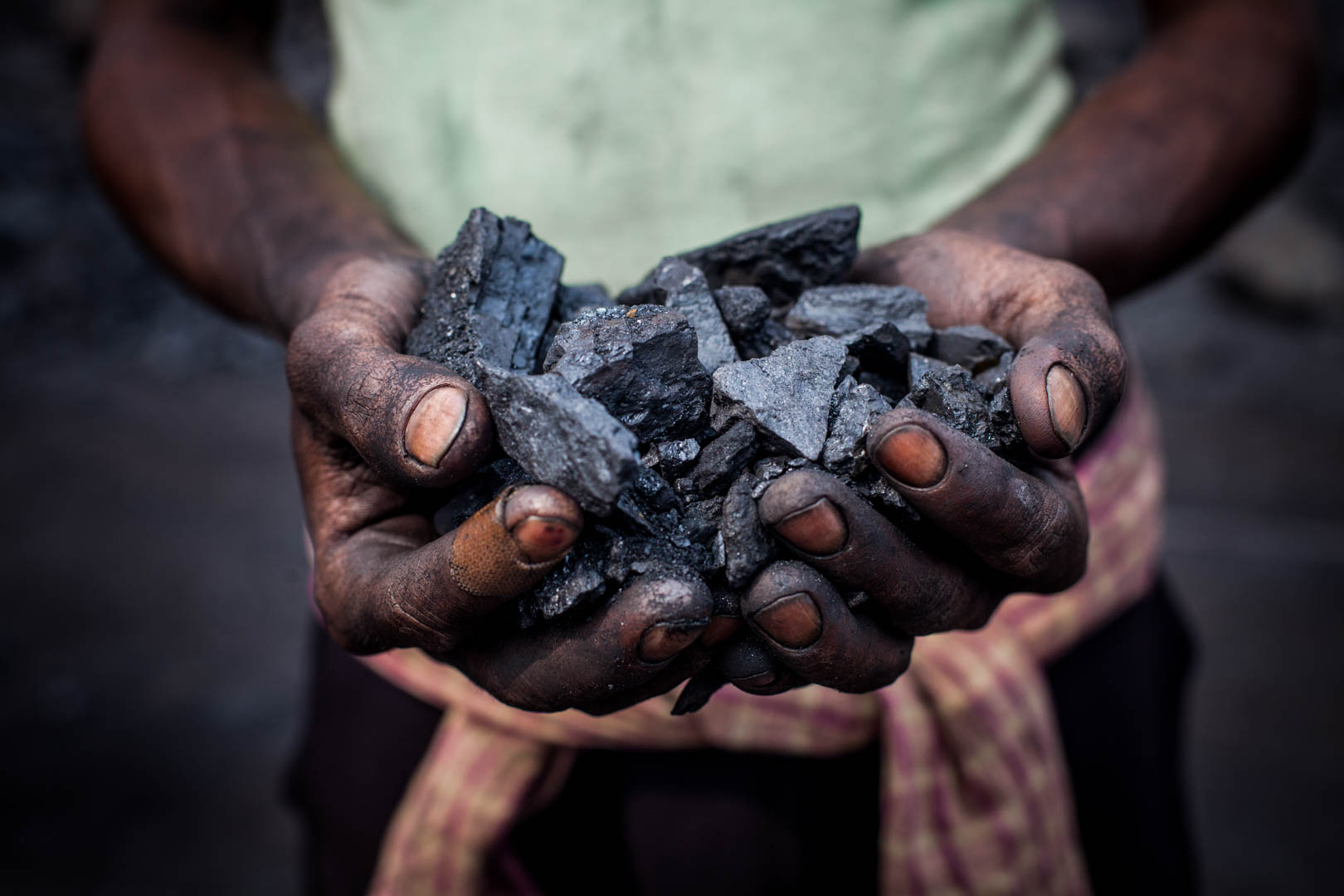 A worker shows a pile of coal that he is holding between his hands.