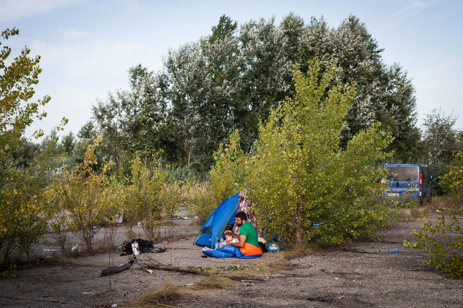 A father comforts his child on a parking lot near the border to Hungary.
