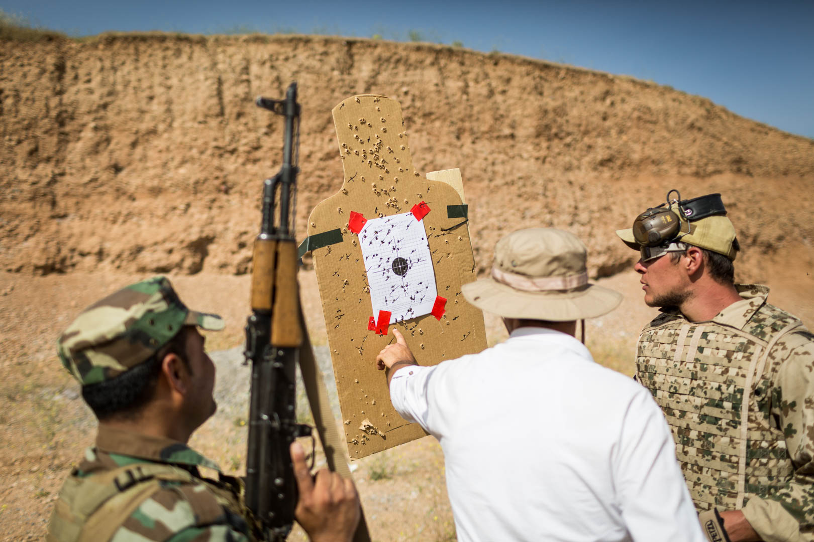 A Peshmerga soldier and his German military adviser are discussing his performance results at the shooting range.