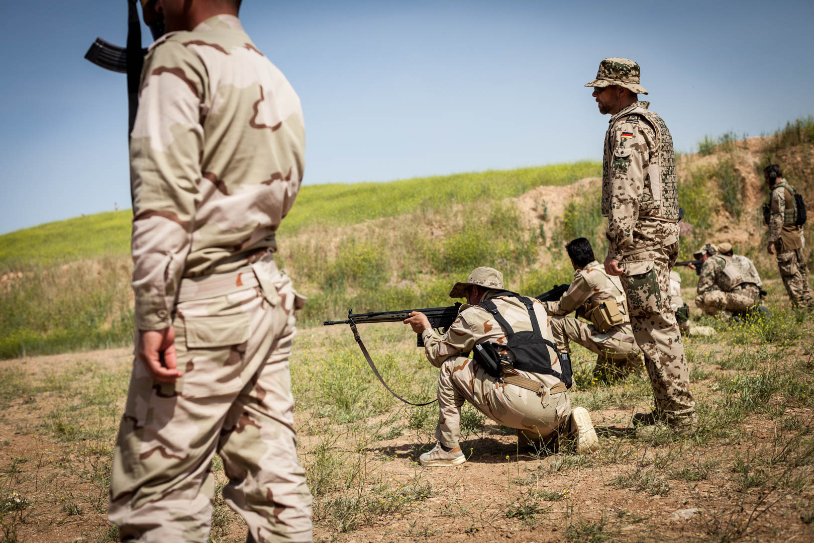Kurdish soldiers are receiving target practice from German military advisers at the shooting range.