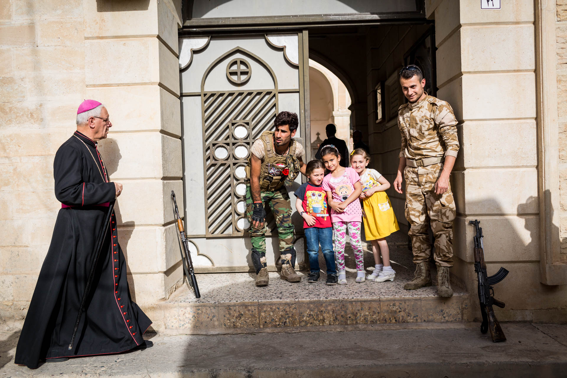 As Ronie and Sargon pose for a picture with a few local kids at the entrance of a church, a priest approaches. Alqosh has a very active religious community and its people have always been proud of their heritage.
