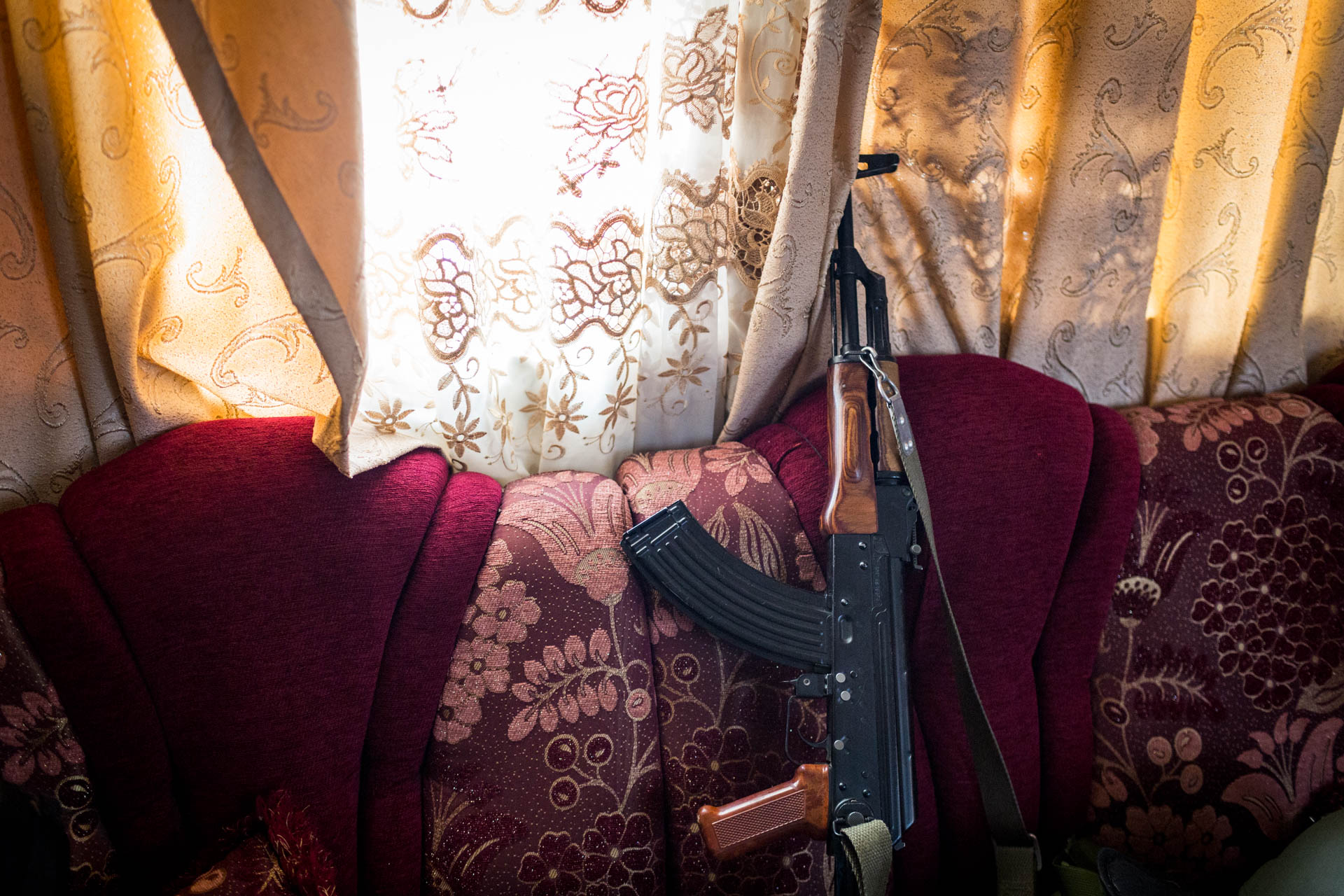 A rifle leans on a sofa in the living room.