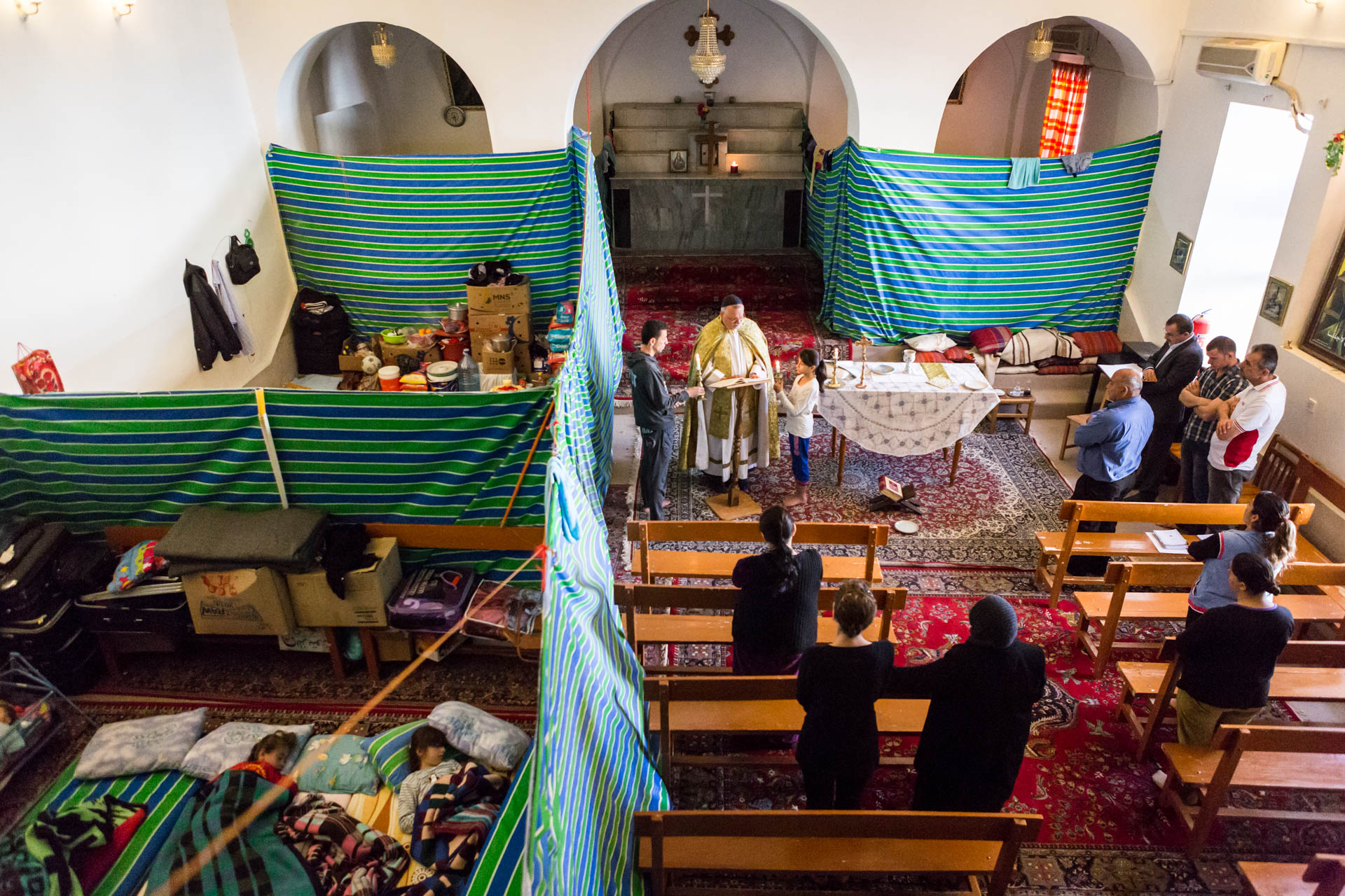 Despite the situation, the church still serves as a sacred place. With four families living in the church, separated by panels of fabric, Father Jens holds a service on Sunday morning.