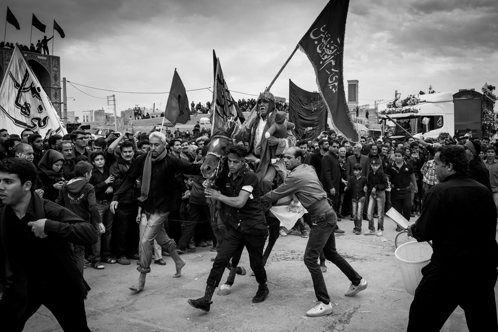 Men are pushing a horse through a crowd of people during the re-enactment of the battle of Karbala.