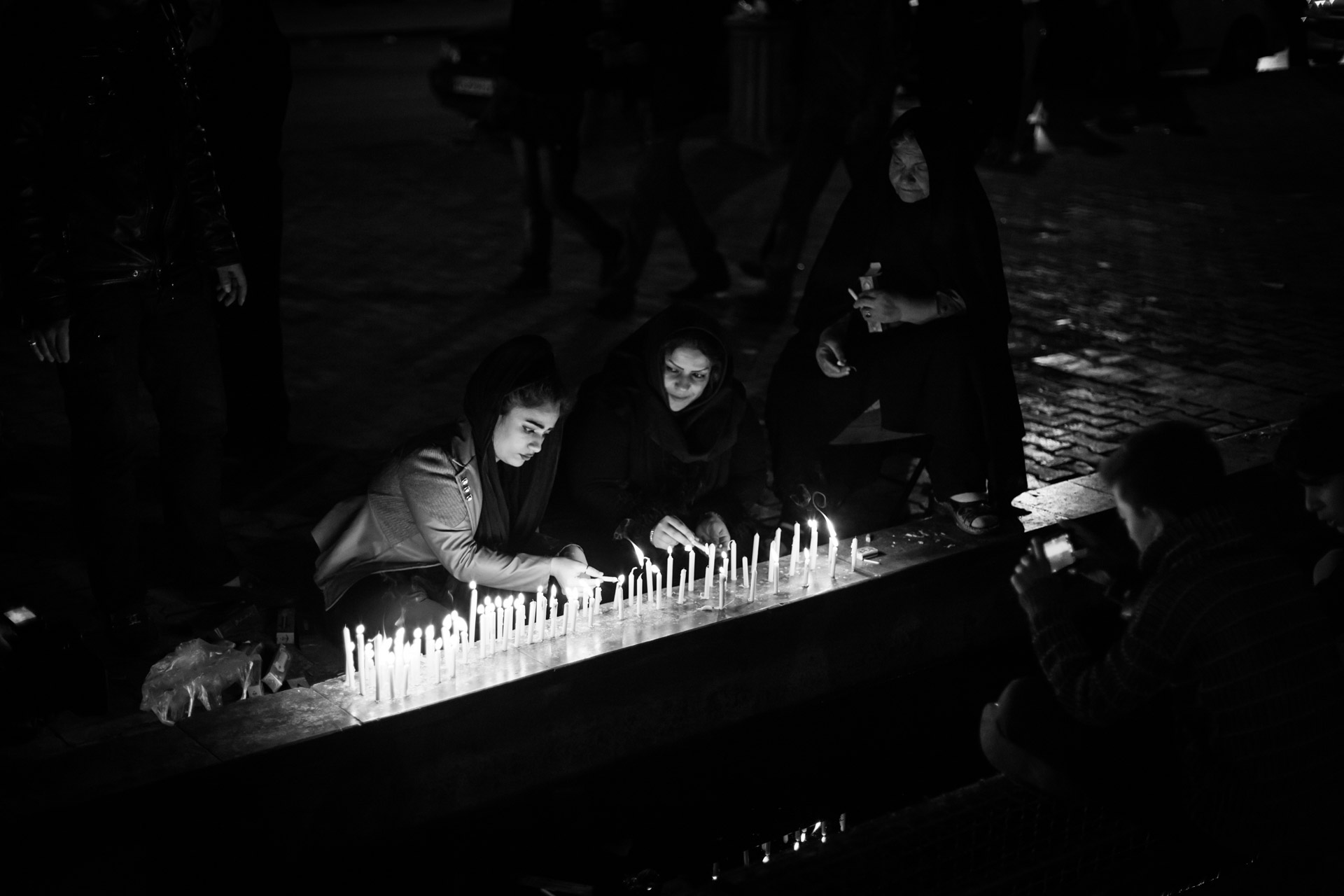 Women are lighting candles at a well in Yazd.