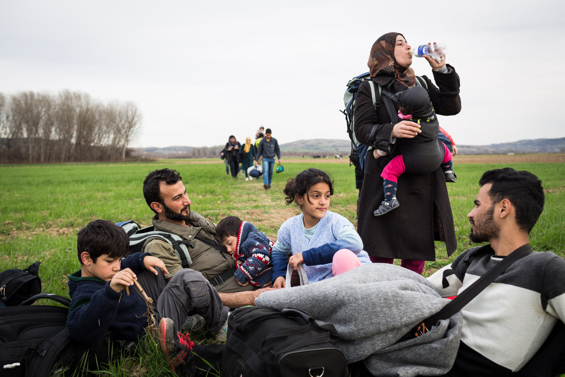 The family takes a last break on the farming fields that surround Idomeni.