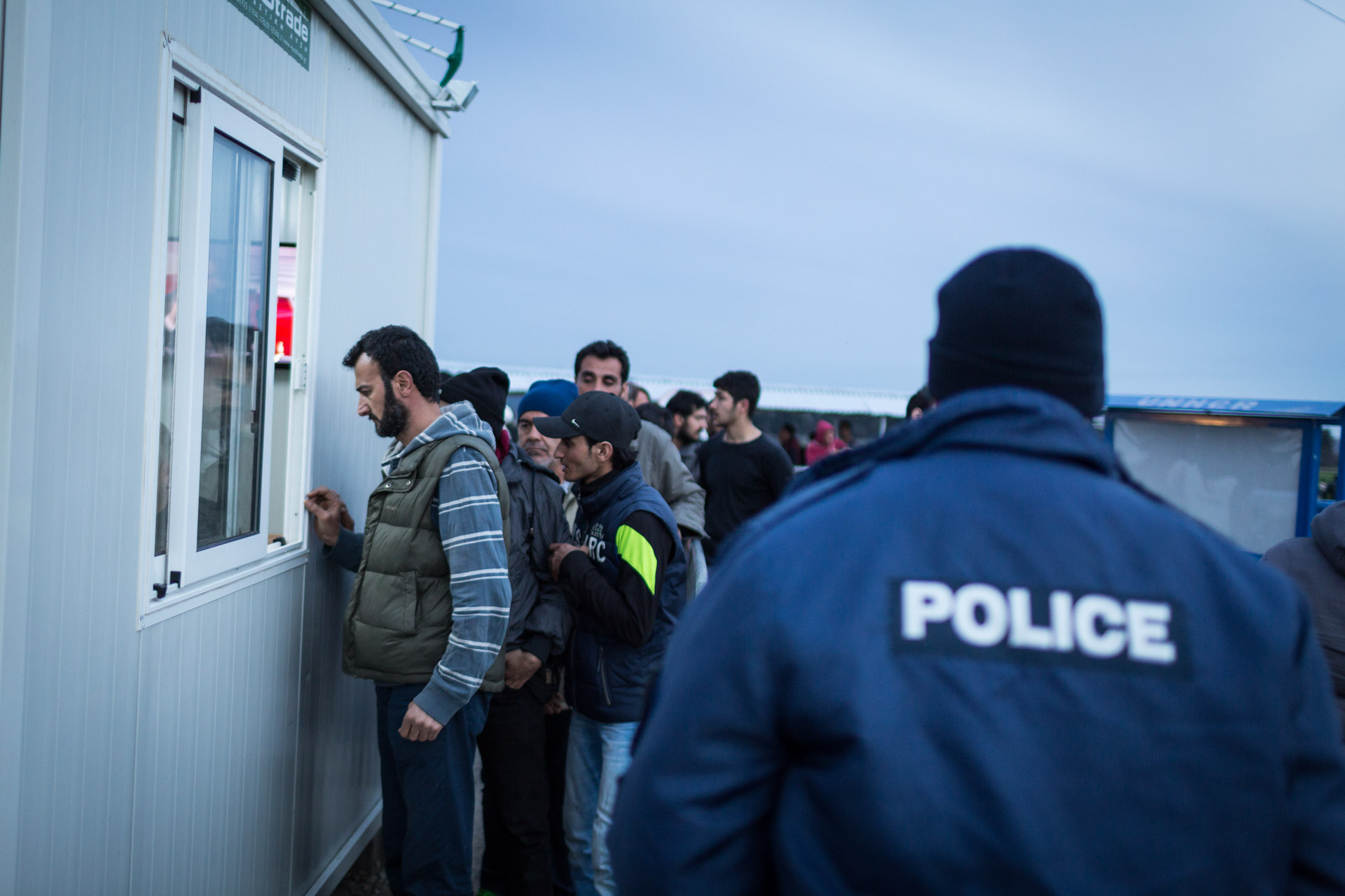 Basem stands in line to get his papers stamped by Greek police in order to get a waiting number. This number will indicate how long his family has to wait to cross the border.