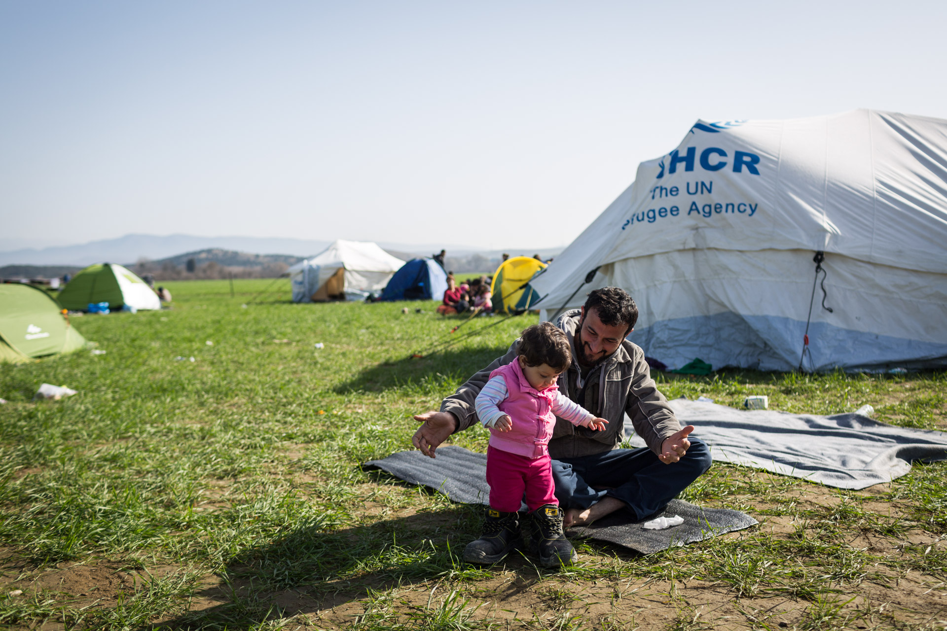 By the end of February, Idomeni was inhabited by maybe 2000 people. It was easy to find free space. Here, Basem puts Lilly in his big shoes. Basem used to work as an engineer in a substation in Syria. He came to Greece in the shoes he needed for work.