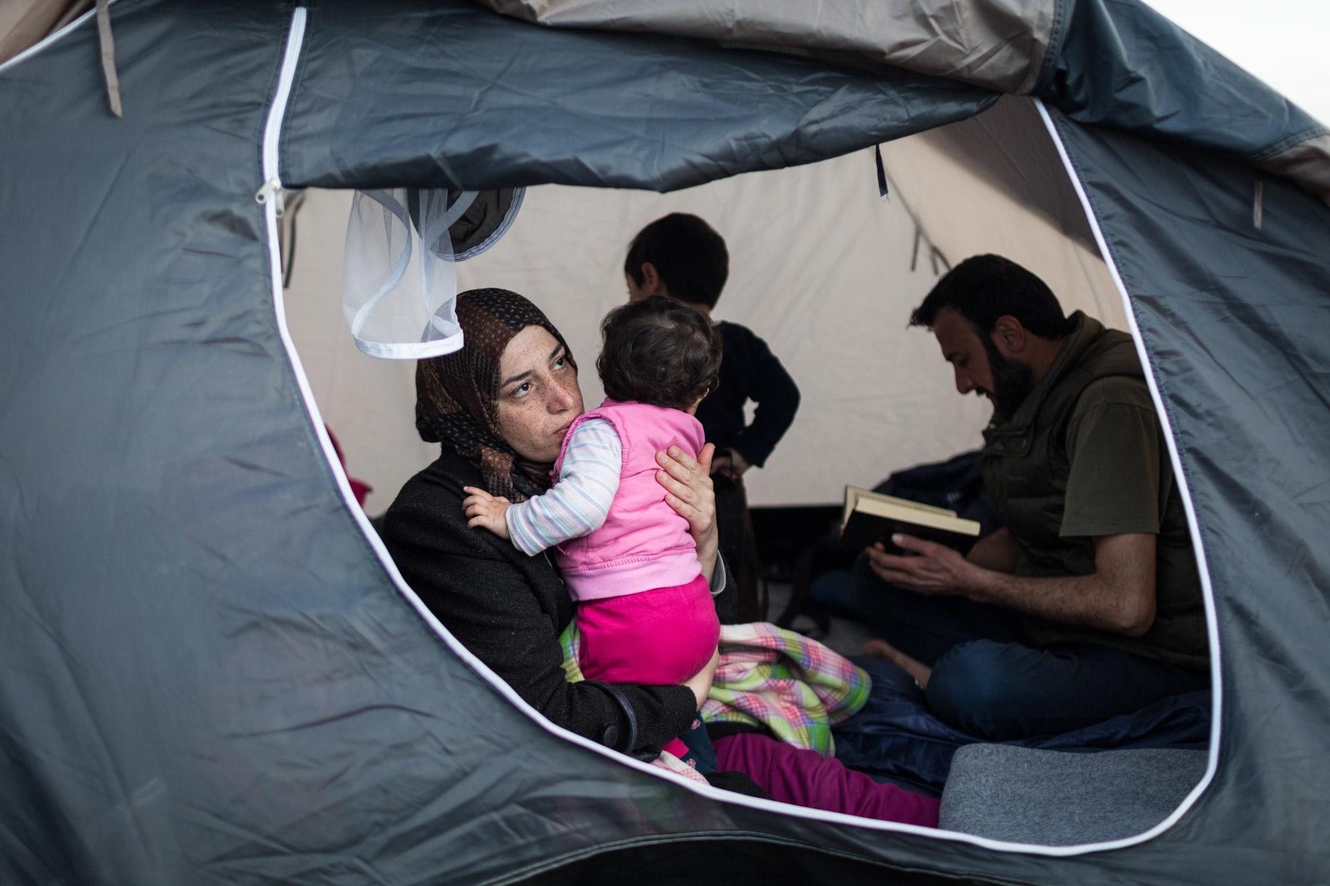 """Khulud, Basem's wife, takes care of Lilly, while Basem reads a Qu'ran in the background. The al-Turkis are Sunni Muslims. In more than two weeks, I never saw them pray once. """"I love it, when my husband reads the Qu'ran"""", says Khulud. """"He is very calm and at peace with himself after reading."""""""
