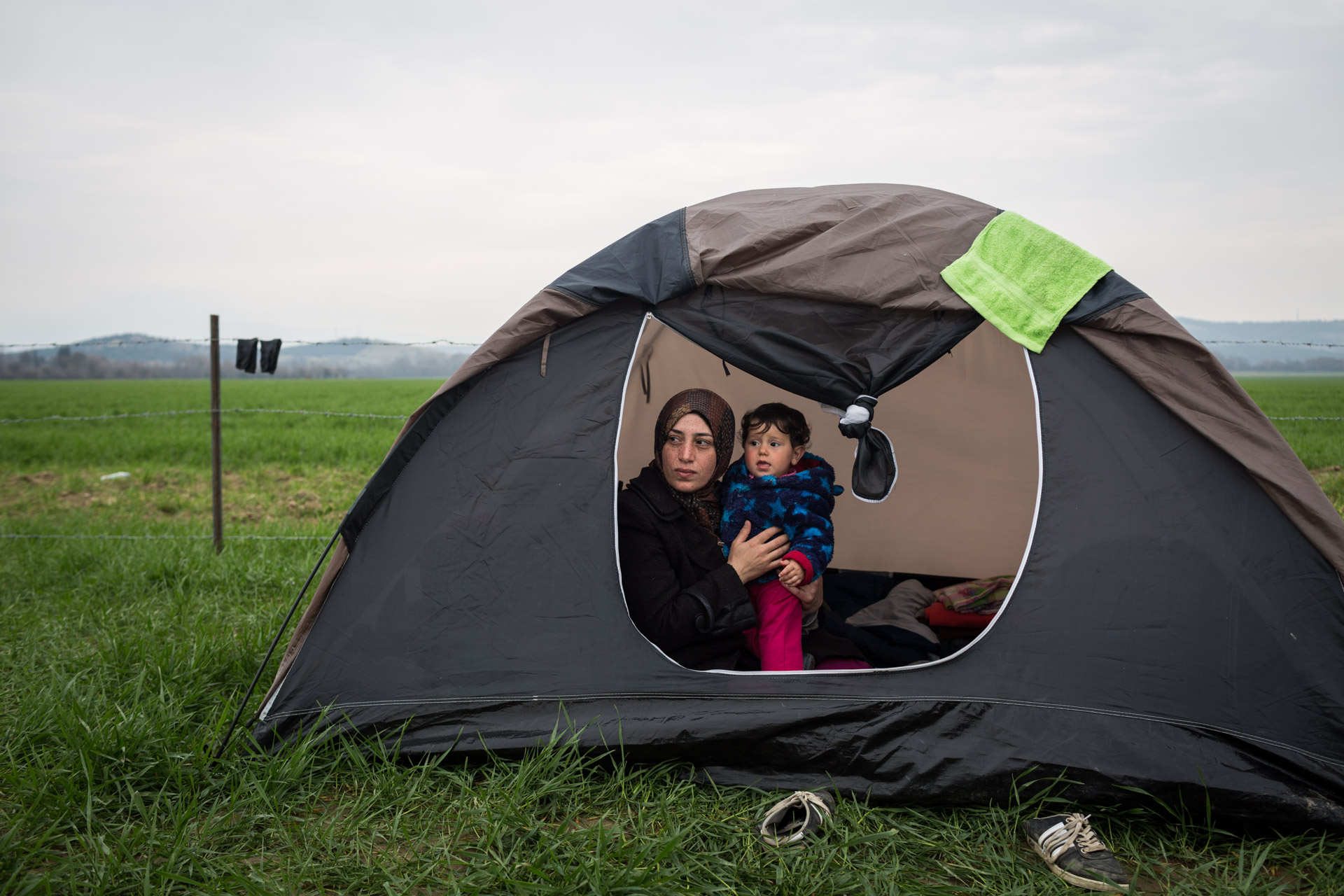 Khulud and Lilly in the tent after having breakfast. After she runs out of clean clothes, she stays mostly in the tent. Khulud feels ashamed because in Idomeni she doesn't have infrastructure to clean her clothes.