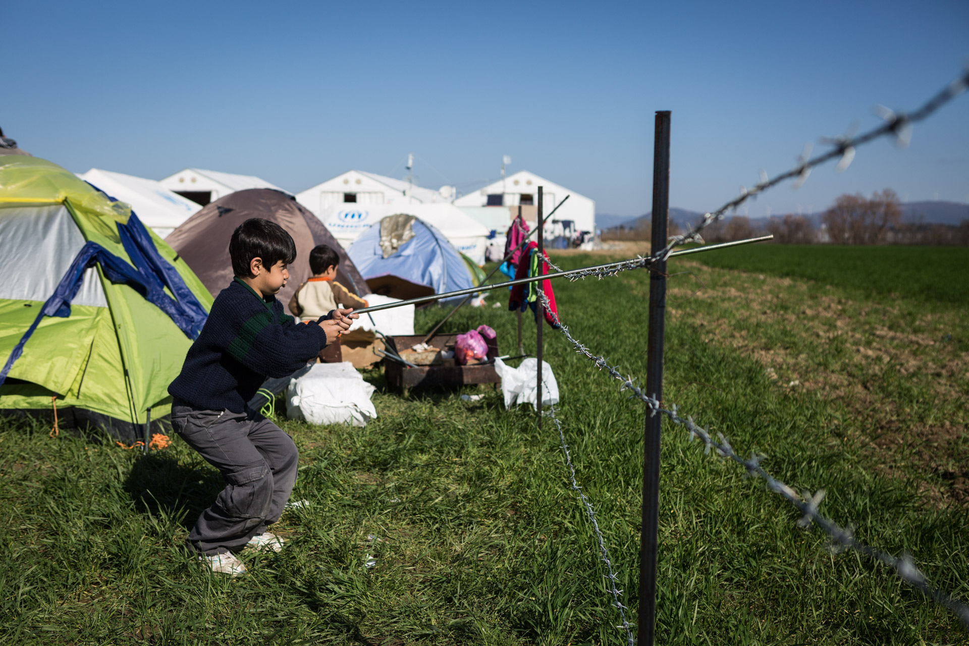 Baker, Basem's oldest son, plays at a fence in Idomeni.