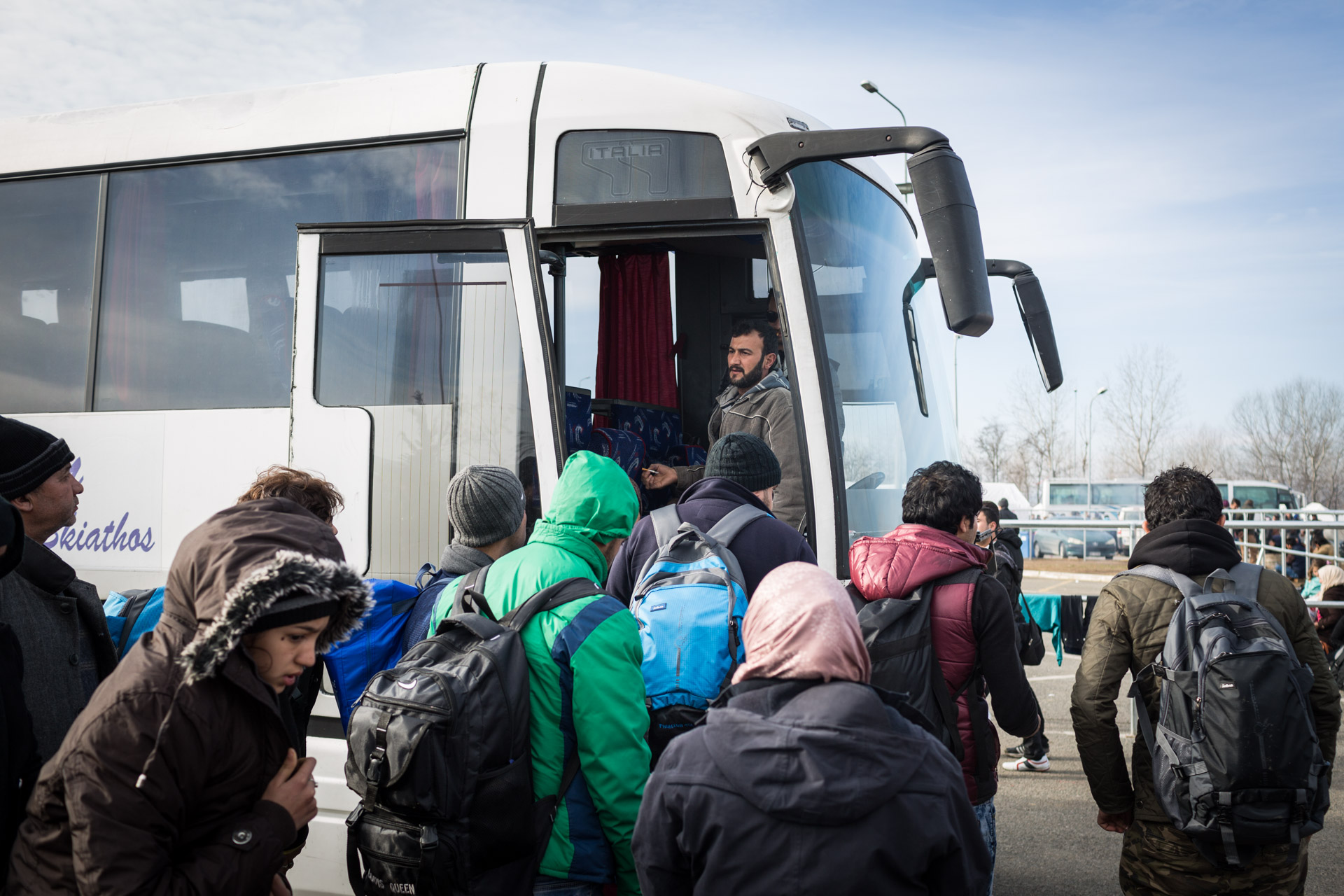 Basem, the father of the family, stands confused in the door of the bus, that was supposed to take the family from Athens to Idomeni. Instead, the bus stopped at a gas station 30 kilometres away. Greece ordered all buses with migrants to stop here.