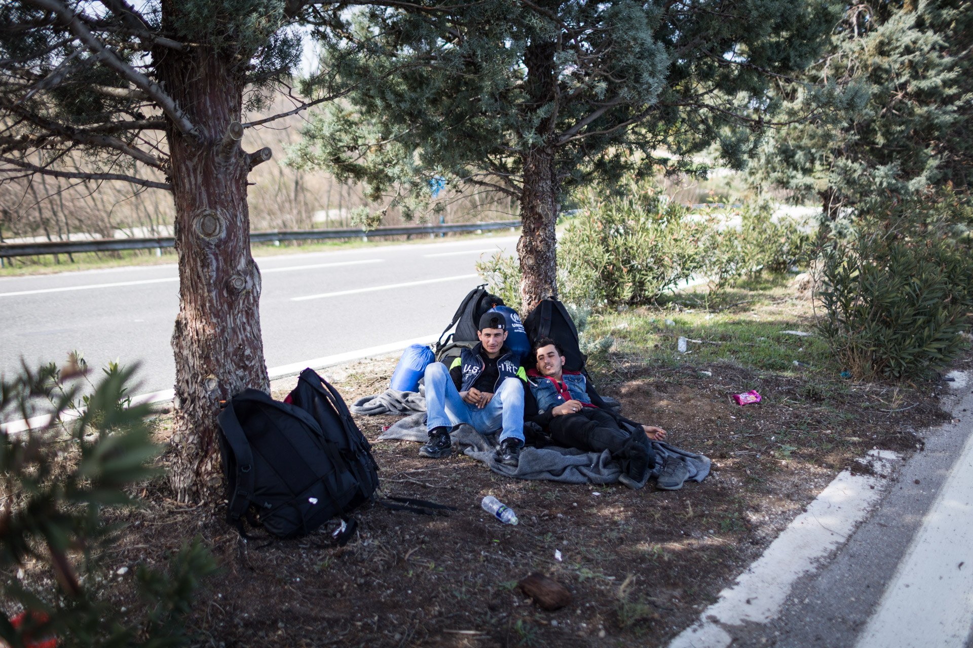 Ahmad and Mohammad, two close friends of the al-Turki family, rest under a tree on the freeway to Idomeni.