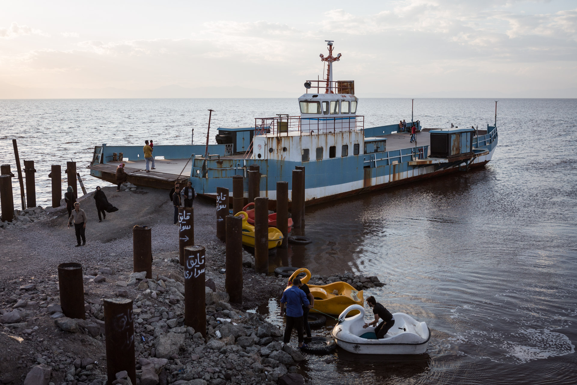 In the evening, people embark an old ferry to await dusk.