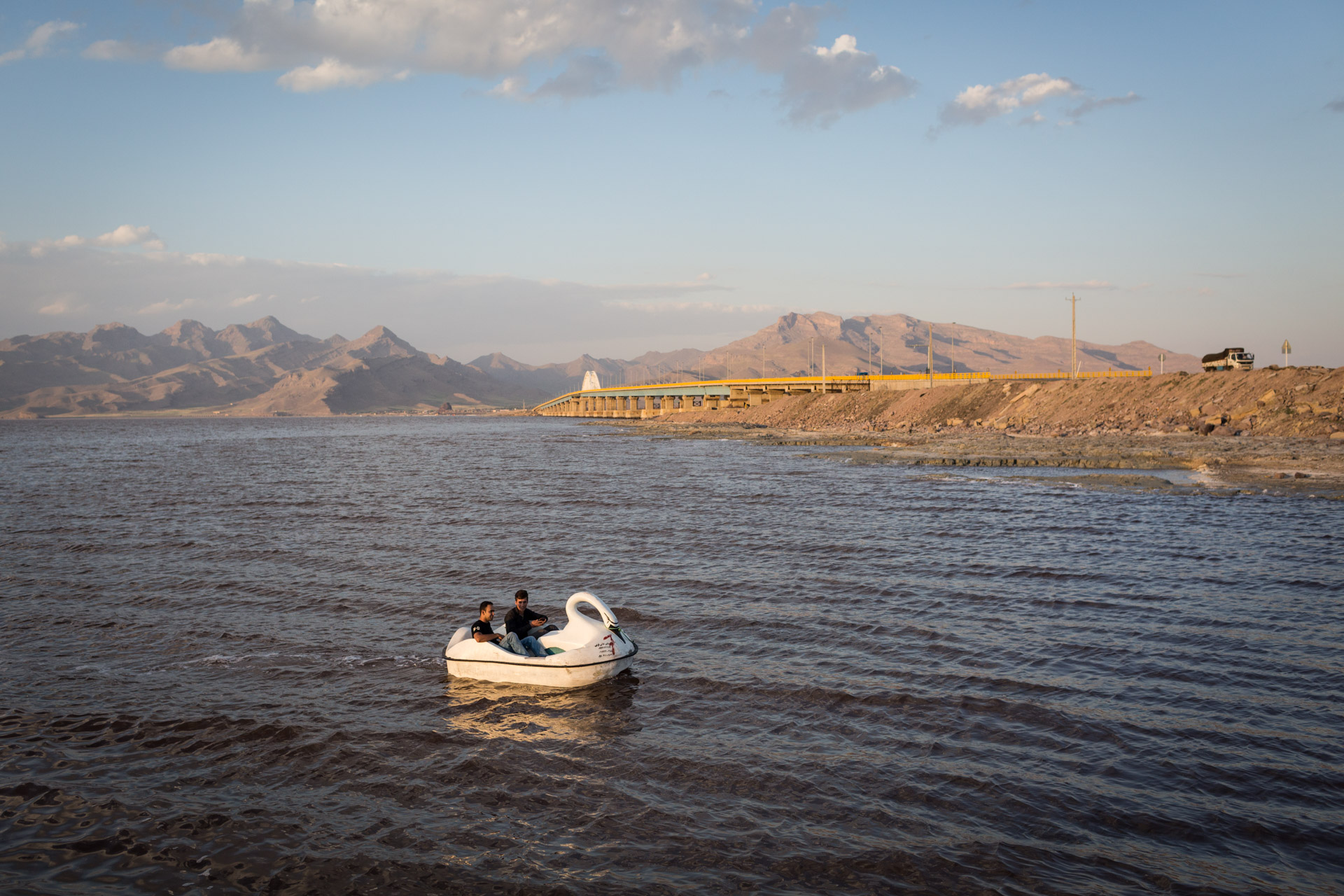 Two men are riding a swan-shaped paddleboat in the northern half of Lake Urmia that still has water.
