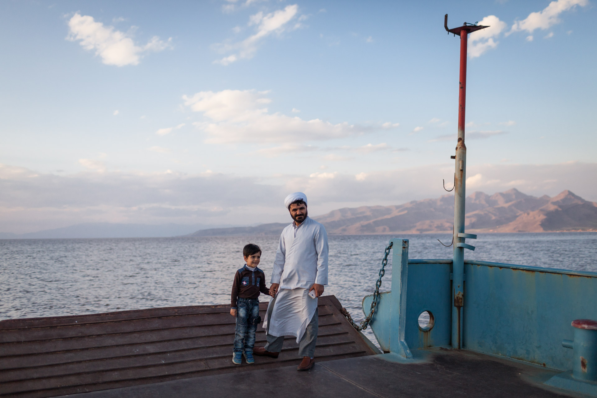 A mullah (a religious clergyman) and his son have their photo taken on the old ferry.