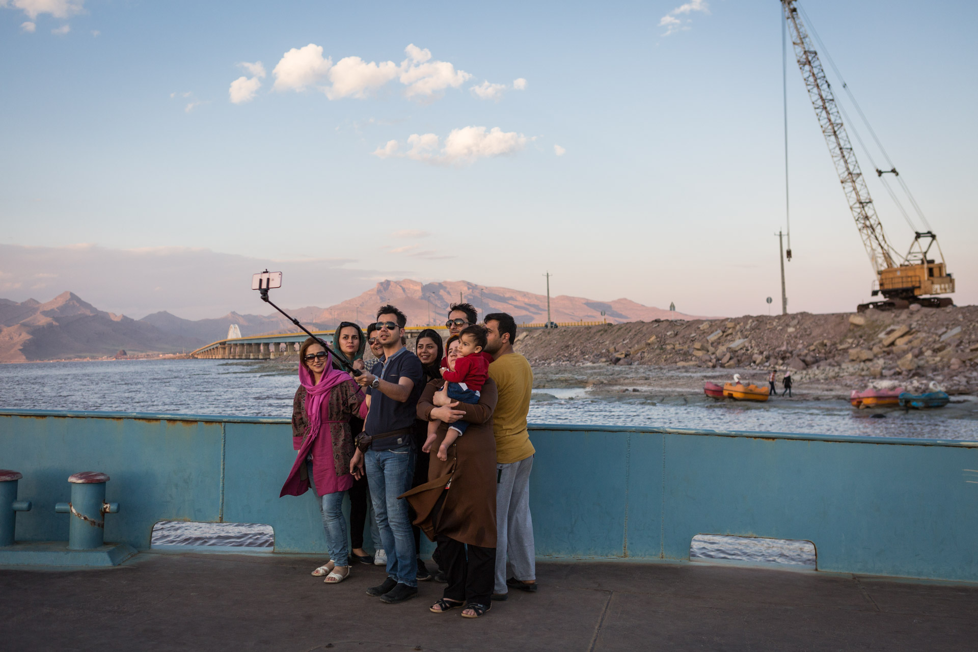 A group of young Iranians take a selfie, the bridge crossing the lake in the background.