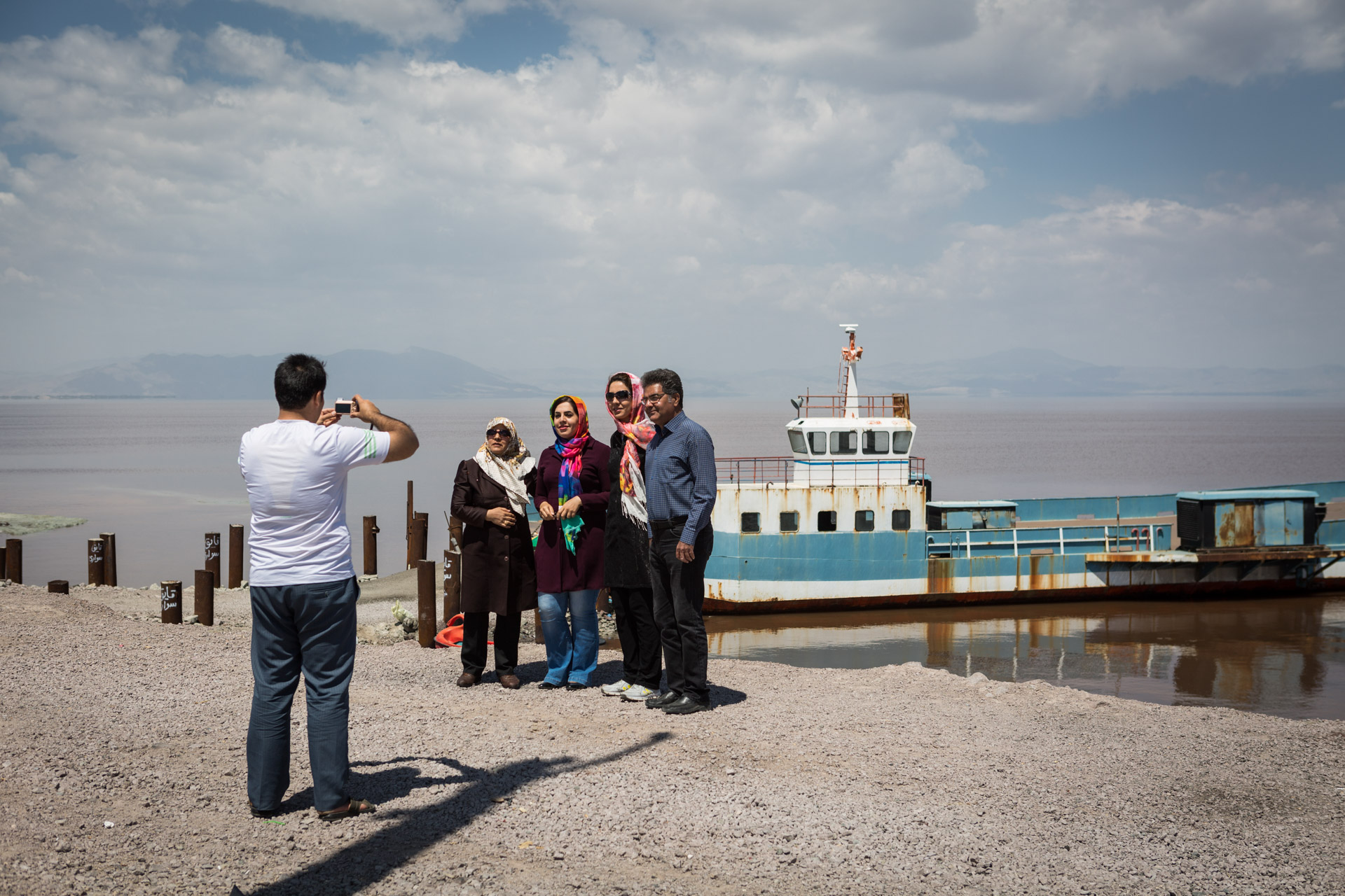 A family has its photo taken in front of the northern half of the lake, which still has water. The ferry in the background has turned into a popular subject for photos, after becoming useless when the bridge connecting the eastern and western half of the lake was finished.
