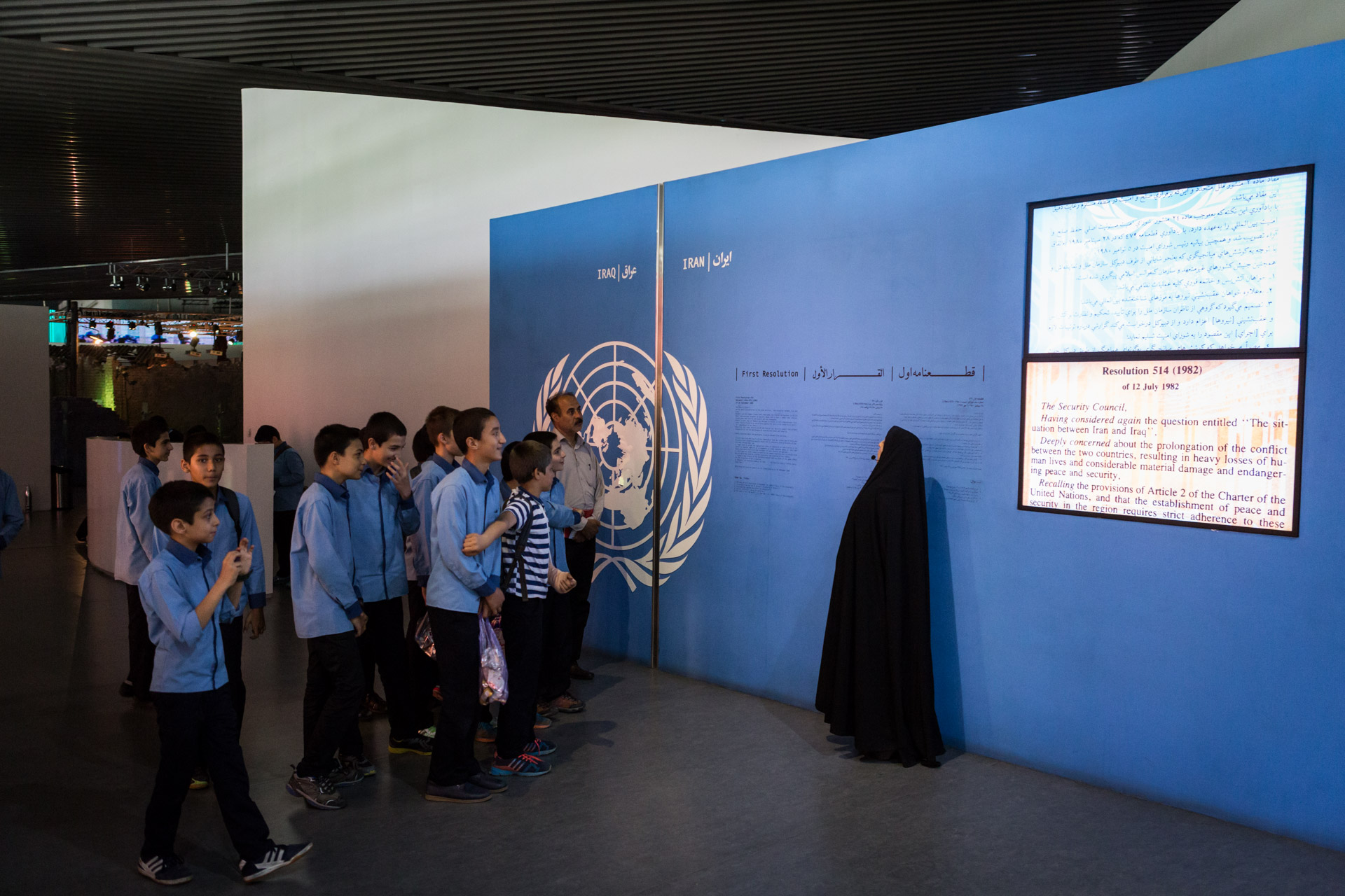 "A female guide in the museum is walking a class through a hall. The museum blames western countries for selling weapons to Iraq and the United Nations for not sanctioning Iraq and calling the start of the war simply a ""situation""."