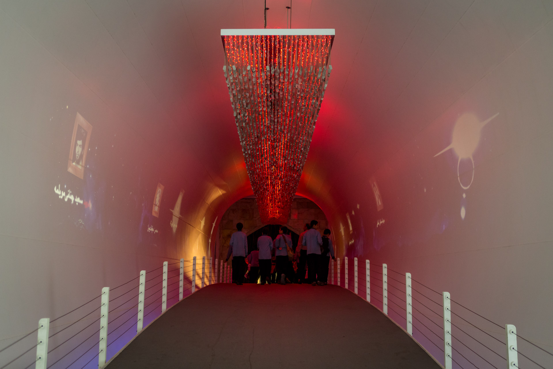 The bridge to the final hall - the hall of martyrdom - is illuminated in red, decorated with dog tags of martyrs of the war, and each side features video art showing photographs of Iranian martyrs ascending upwards, while turning into little stars. Metaphorically, the visitor takes a bridge into heaven.