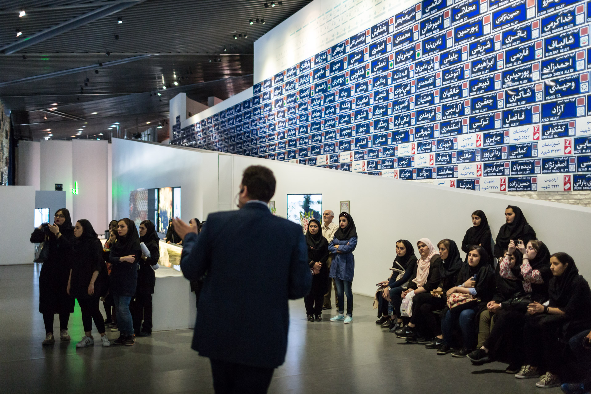 A male guide explains a video to a female class in the museum's hall of martyrdom. The blue signs in the back represent a Iranian village destroyed by war each.
