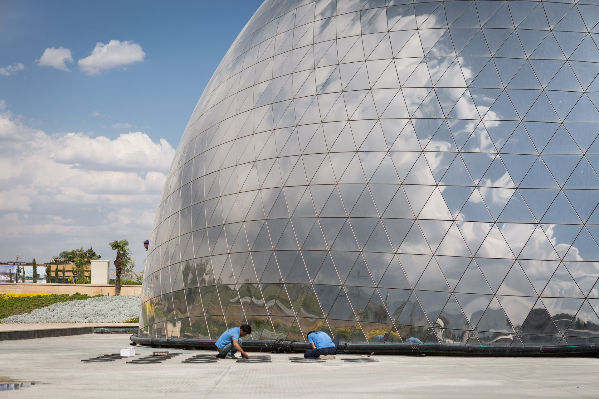 Two workers set their finishing touches to the dome which will feature a 360 degree panorama view of the destroyed city of Khorramshahr.