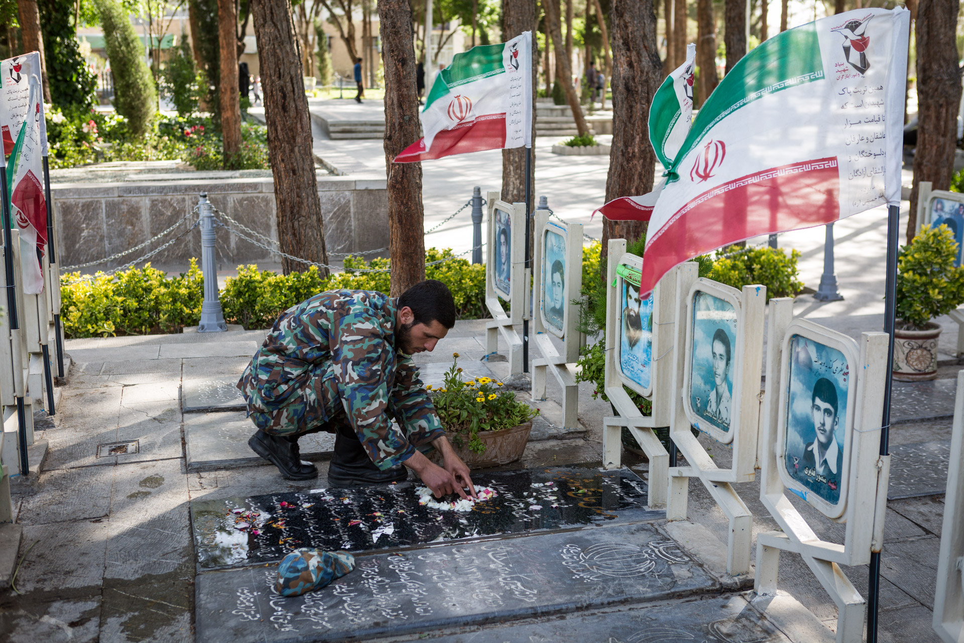 An Iranian soldier spends time at the grave of a fallen martyr.