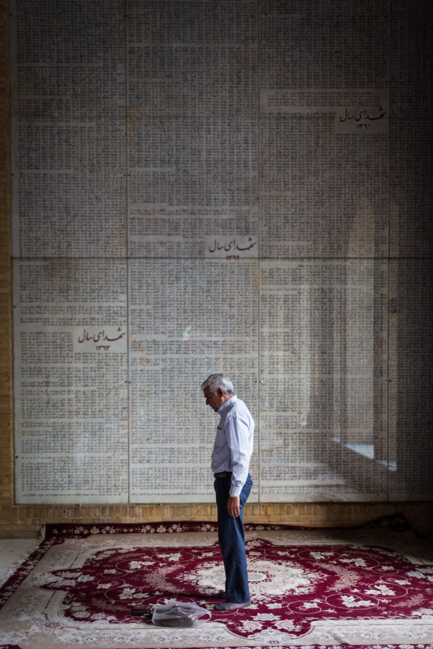 A man prays in front of a list with names of martyrs of the Iran-Iraq war.