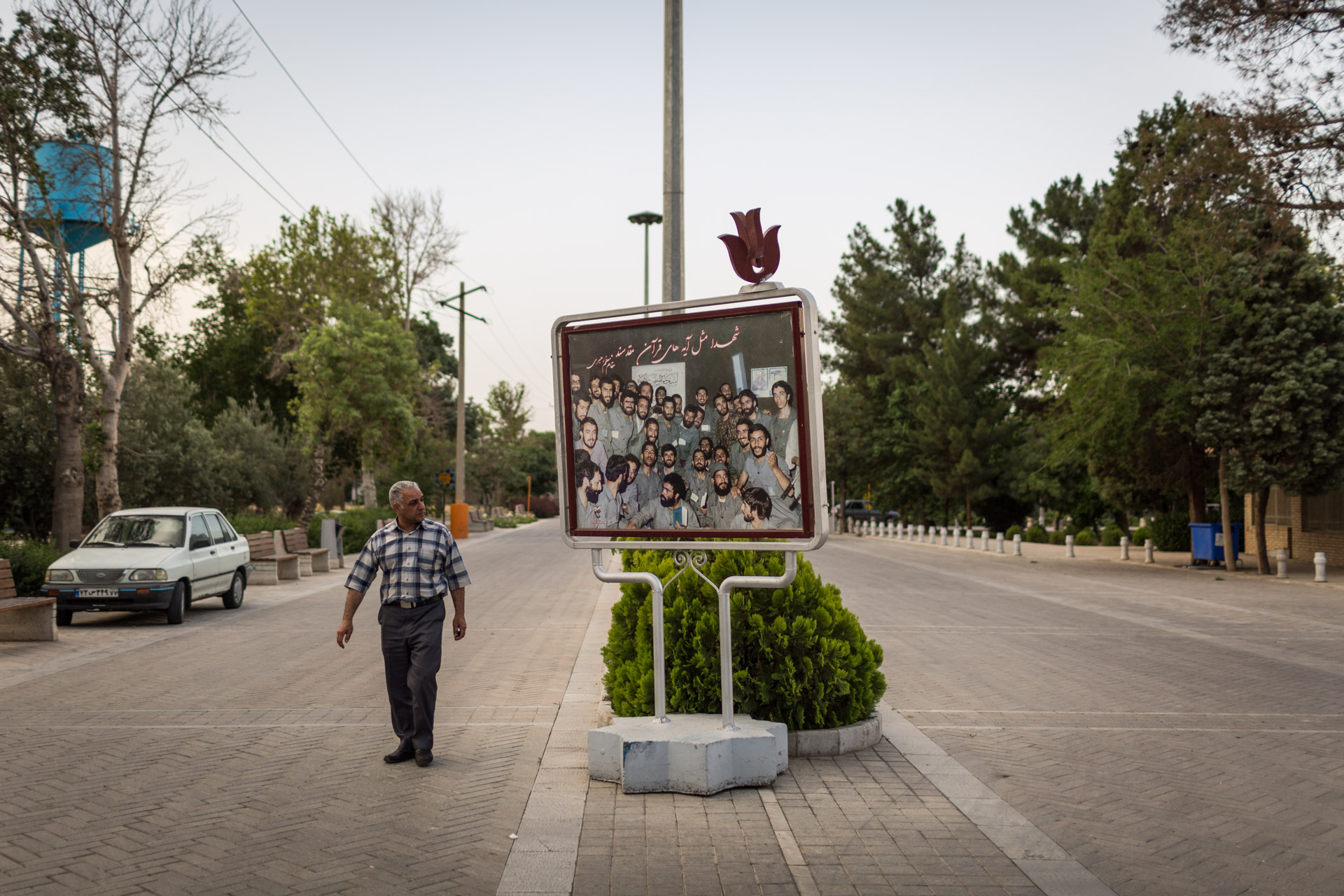 On Behesht-e Zahra, a man walks by a photograph depicting Iranian soldiers during the Iran-Iraq war.