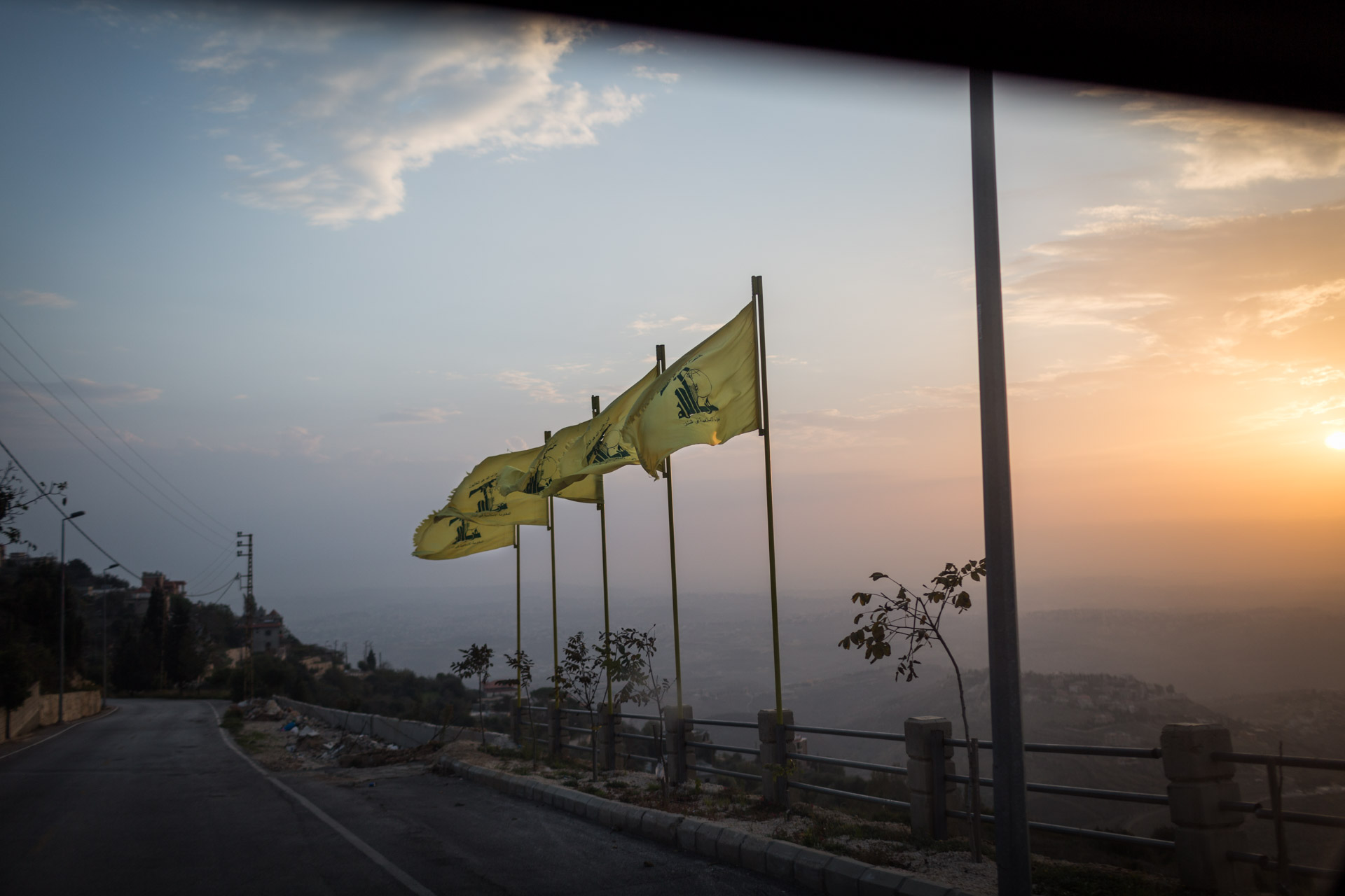Flags of Hezbollah are waving during dusk on a road to Mleeta in Lebanon.